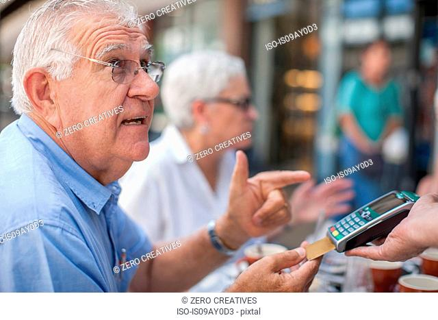 Mature friends sitting at cafe, senior man paying bill with credit card