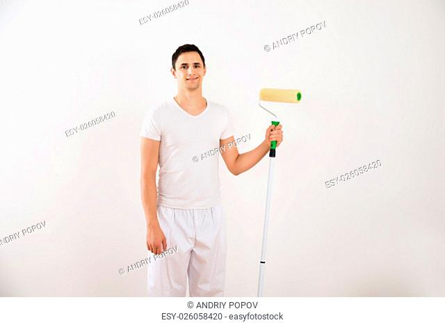 Portrait of smiling young man holding paint roller while standing against white wall at home