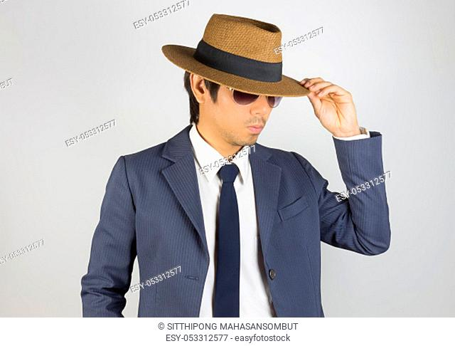 Young Asian Portrait Businessman in Navy Blue Suit Wear Sunglasses and Touch Hat Brim at Front View Pose on Grey Background