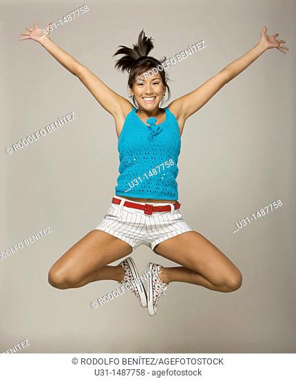 Latin woman jumping happily in a studio setting