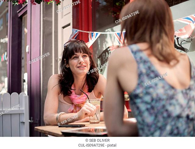 Two female adult friends chatting whilst sitting outside traditional pub