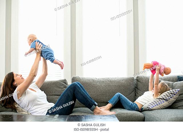 Mother holding baby boy in air across from daughter holding doll in air