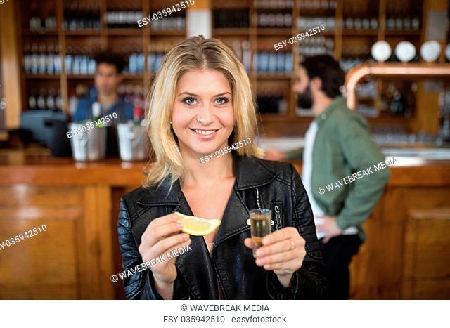 Beautiful woman having tequila shot in bar