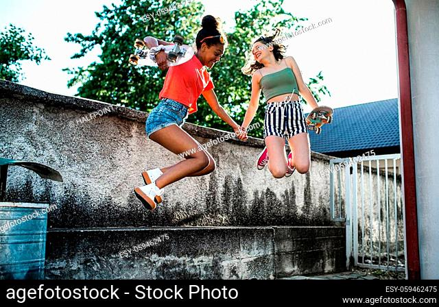 Young teenager girls friends with skateboards outdoors in city, jumping by concrete wall