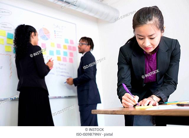 Businessman and businesswomen, in office, brainstorming, stick ideas to whiteboard