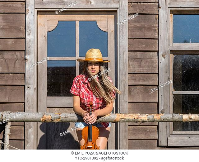 Country-girl with violin in hands in wild west environment. Croatia