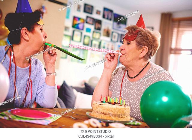 Senior women blowing party favor at each other