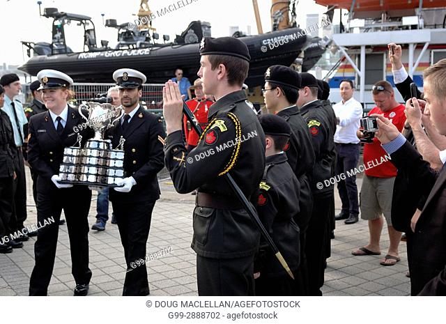 A cadet honour guard and spectators watch as two officers carry the Memorial Cup trophy