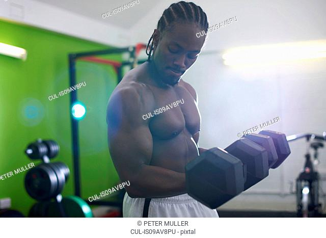 Bodybuilder lifting dumbbell in gym