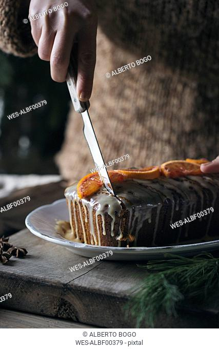 Woman's hand cutting home-baked Christmas cake, partial view