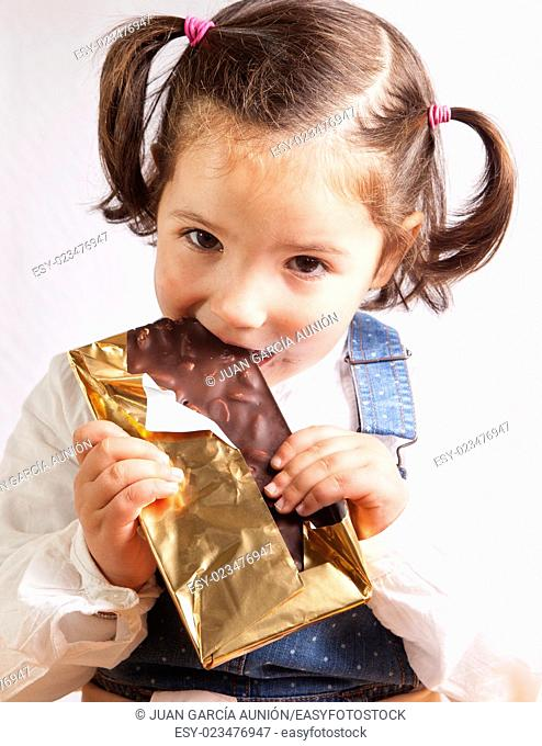 Portrait of happy girl eating chocolate. Isolated over white background