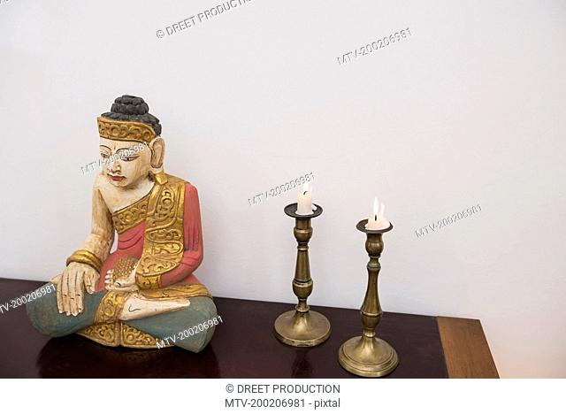 Buddha statue in lotus position with two candles, Munich, Bavaria, Germany