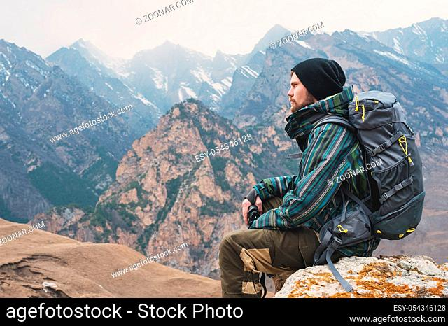 Tired bearded hipster with binoculars in his hands sits on a stone among the Caucasian mountains and looks out into the distance