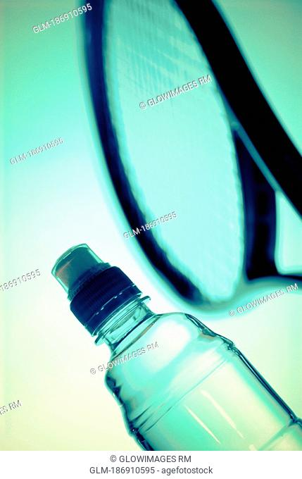 Close-up of a water bottle and a tennis racket