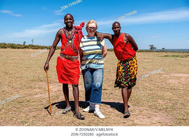 MASAI MARA,KENYA, AFRICA- FEB 12 Masai men in traditional clothes and European tourists, review of daily life of local people