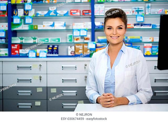 Beautiful smiling young woman pharmacist doing her work in pharmacy