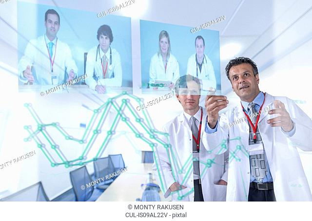 Medical specialists discussing results through video conference on futuristic display