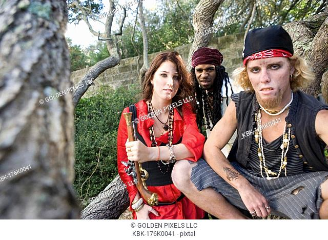 Portrait of pirates sitting under trees with woman pirate holding a gun