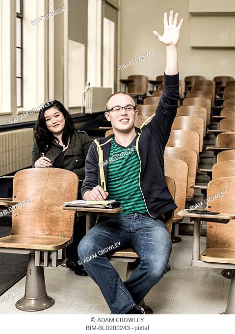 Student raising his hand in classroom