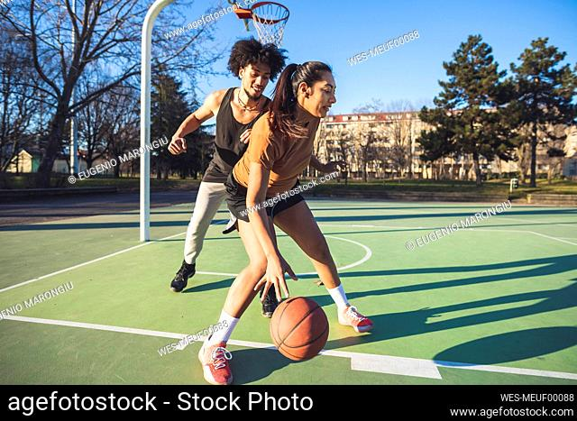 Young man and woman playing basketball on court