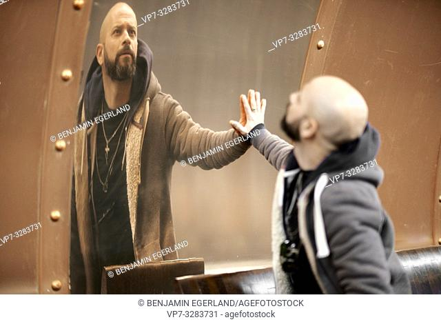 man looking at his distorted self in mirror in Paris, France