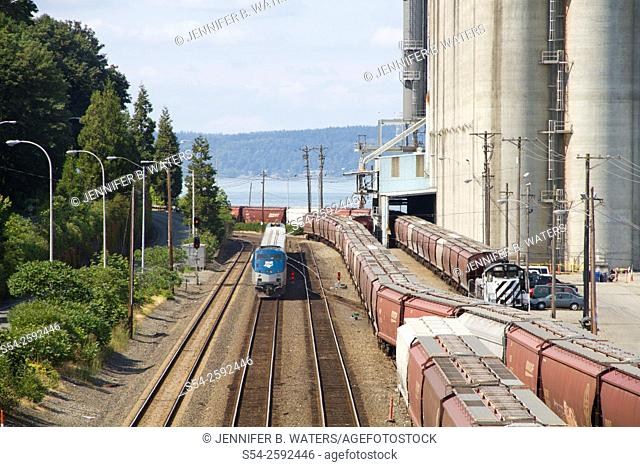 An Amtrak Talgo passenger train just west of downtown Tacoma, Washington, USA near a grain export company in Commencement Bay