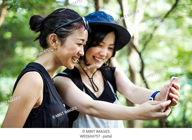 Two young women standing in a forest, taking a selfie