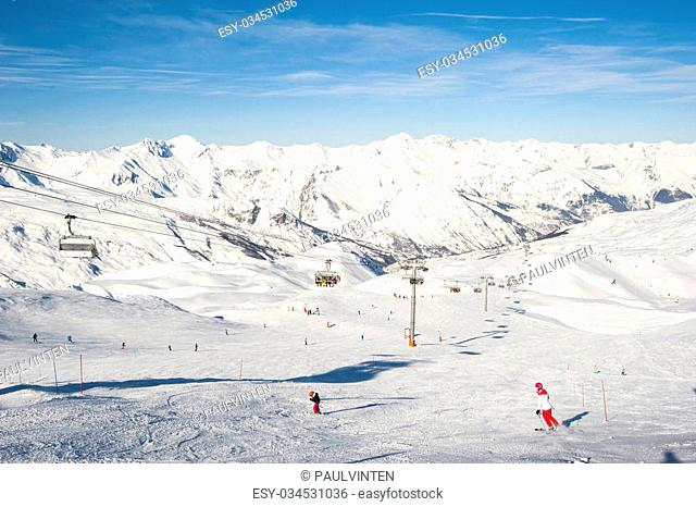 View down a ski piste with skiers and chairlift on mountains