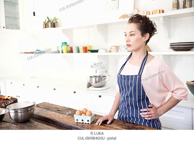 Young woman standing at kitchen counter with carton of eggs