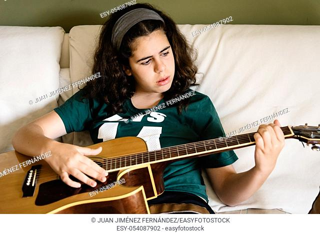 Girl practicing chords on acoustic guitar at home sitting on bed