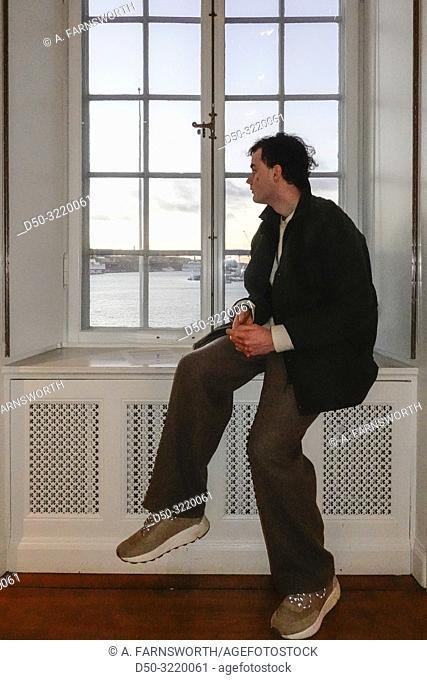 Stockholm, Sweden An 18 year old boy athr Waldermarsudde art musuem sitting below a statue