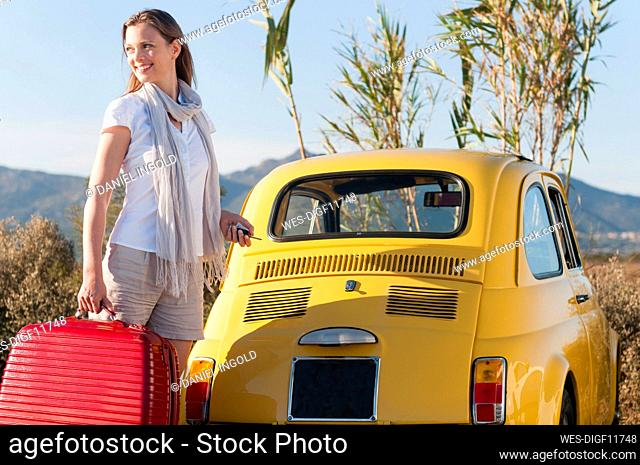 Smiling woman with suitcase standing in front of yellow vinage car, Sardinia, Italy