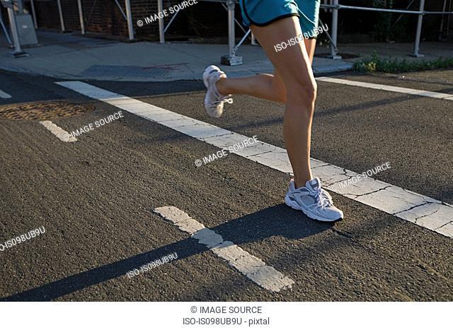 Legs of runner on road