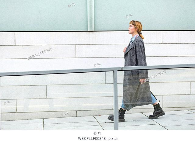 Self-confident young woman wearing grey coat walking on a ramp