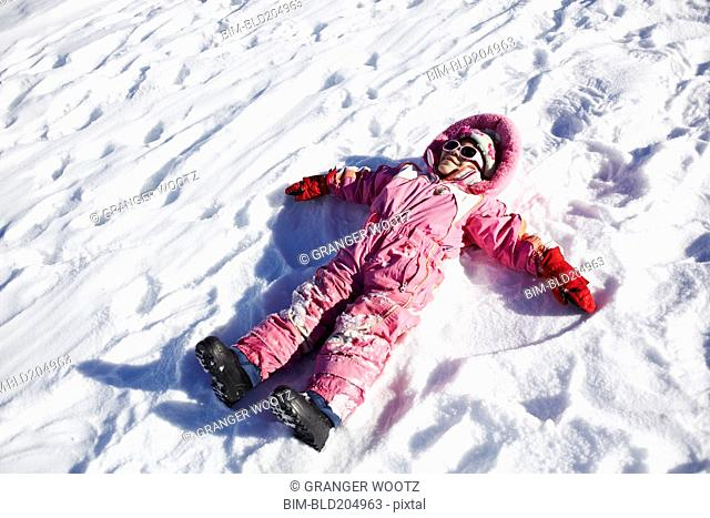 Mixed race girl making snow angels