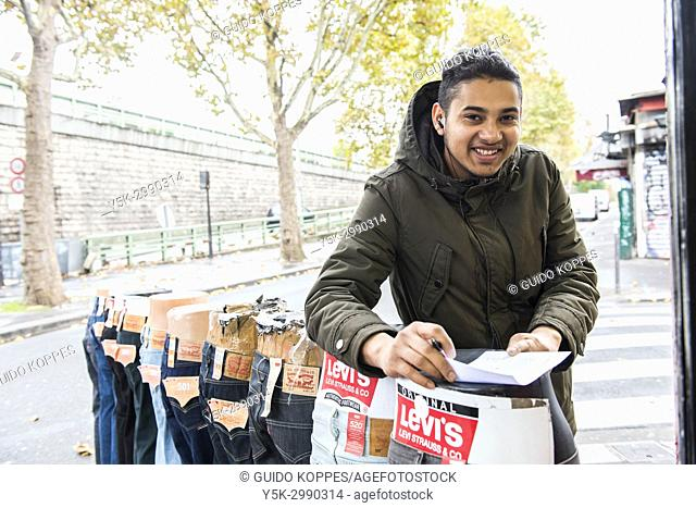 Paris, France. Young, male immigrant to the French Republic, being proud to have his own fashion store at Saint-Denis commercial district