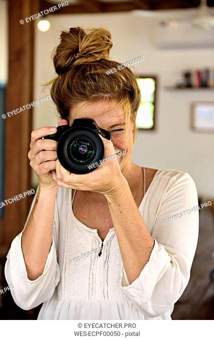 Portrait of laughing young woman taking picture with camera