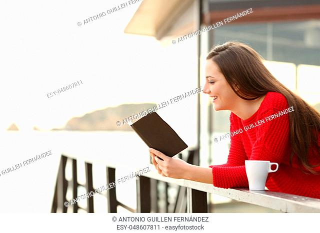 Side view of happy woman wearing a red sweater reading an ebook in an hotel or apartment on the beach on holidays