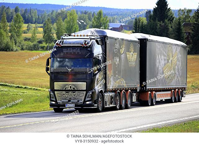 JAMSA, FINLAND - AUGUST 23, 2018: The spectacular show truck Volvo FH16 Ace of Spades transports load on scenic road in Central Finland in late summer