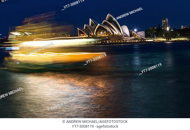 Fiery looking Ferry at dusk with Harbour bridge and Opera house, Sydney, New South Wales, Australia