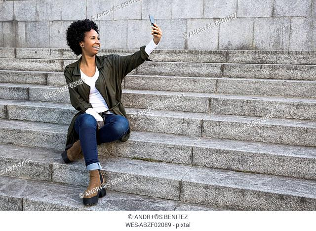 Smiling young woman sitting on stairs taking selfie with smartphone