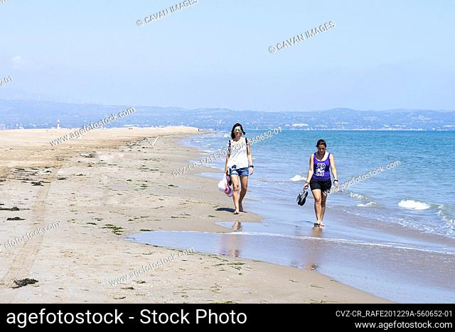 Front view of two women walking barefoot on seashore at beach
