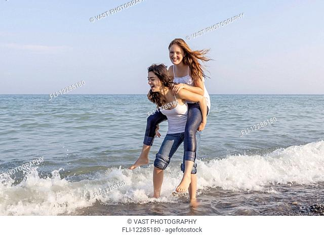 Two girls playing piggyback at beach; Toronto, Ontario, Canada