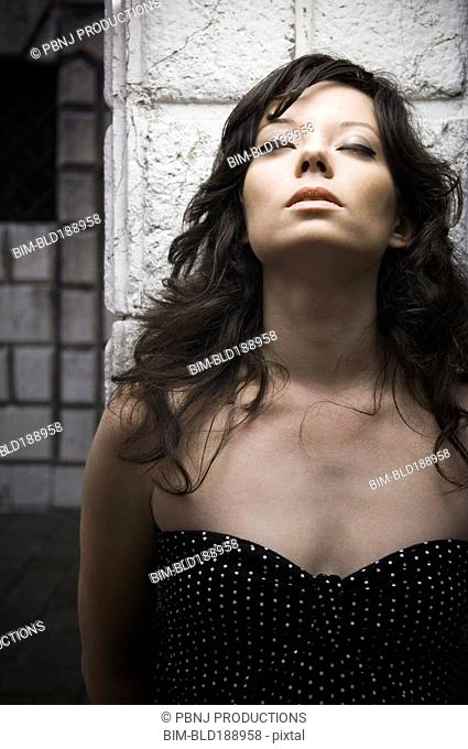 Italian woman leaning against wall with eyes closed