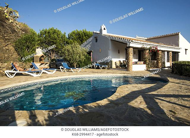 A man relaxes by the pool at a house in the country near Competa, Malaga province, Spain