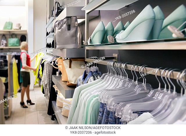 Woman, buyer in fashion shop aisle. Retail outlet with row of hangers, clothes. Fashion store interior