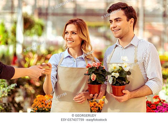 Beautiful young woman and man in aprons are holding plants and smiling while standing in orangery. Another man giving a credit card