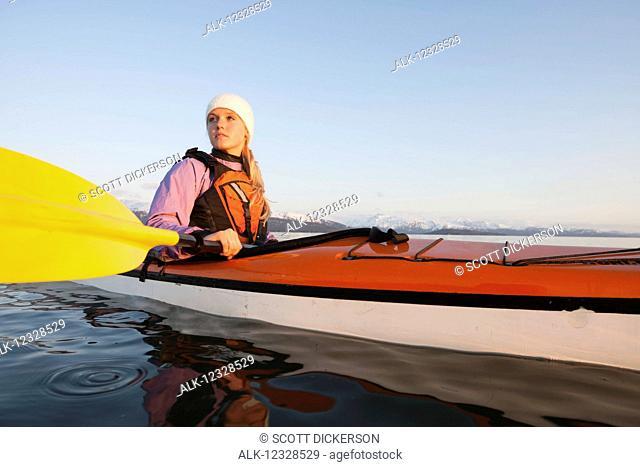 Woman sea kayaking in Kachemak Bay, near Homer, South-central Alaska; Alaska, United States of America