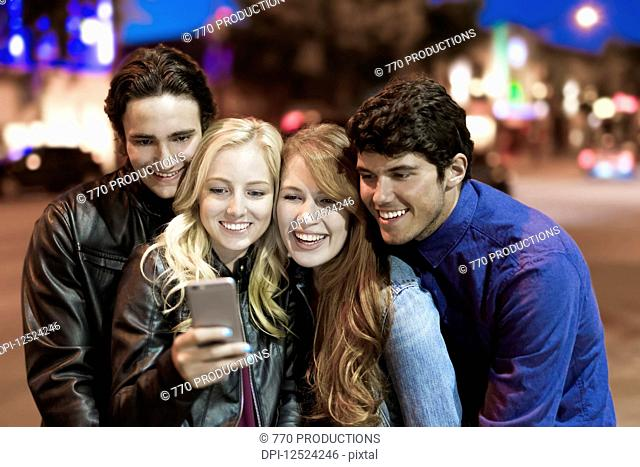 A group of four friends huddle together on a sidewalk looking at a smart phone as the glow from the screen lights up their faces; Edmonton, Alberta, Canada