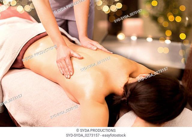 woman lying and having back massage at spa parlor